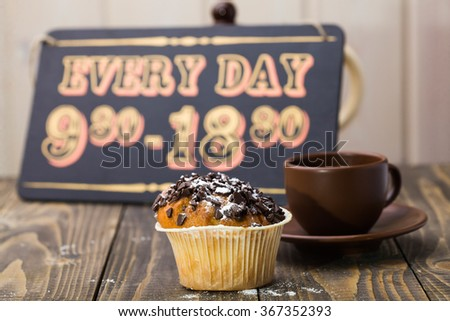 Beautiful yummy fresh muffin and brown cup of coffee on saucer in background of retro wooden sign board with completion schedule of cafe break time indoor closeup, horizontal picture - stock photo