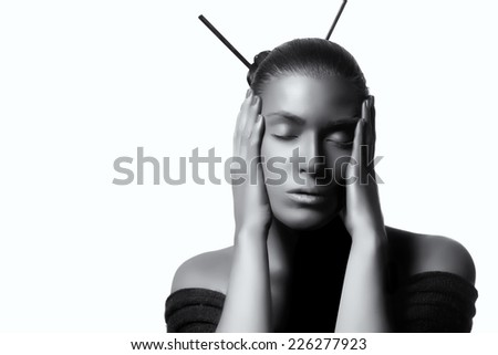 Beautiful zen woman with hands to the sides of the face and eyes closed expressing serenity. High fashion portrait in black and with copy space for text. - stock photo