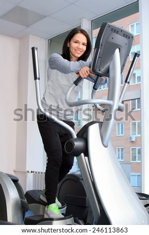 Beautifull female during exercise on a elliptical traner - stock photo