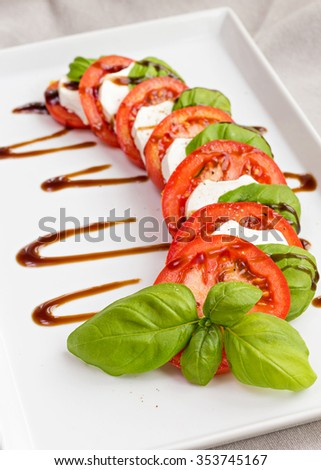 Beautifully arranged tomato, fresh basil and goat cheese served on white plate and decorated with balsamic vinegar - stock photo
