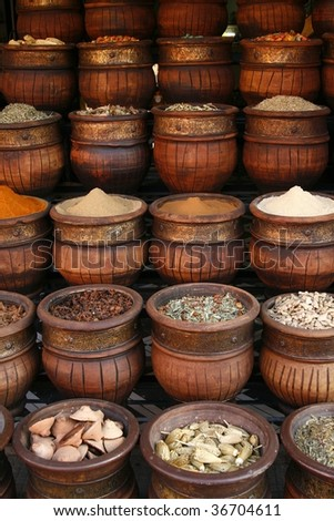 Beautifully carved handmade pots full of aromatic spices on the marketplace - stock photo