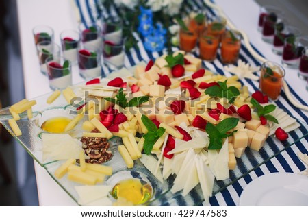 Beautifully decorated catering banquet table with a variety of different cheese assortment sliced on a plate, on corporate christmas birthday kids party event or wedding celebration - stock photo