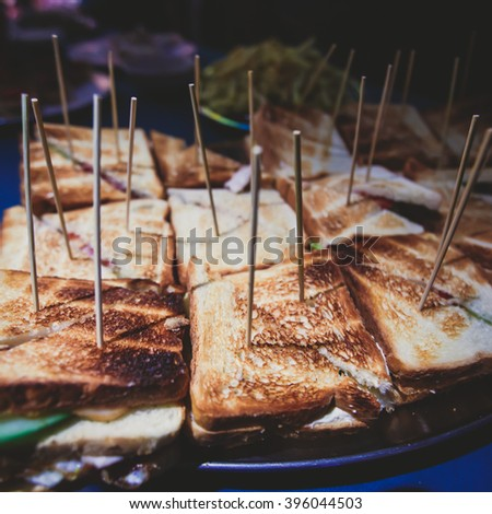 Beautifully decorated catering banquet table with different toasted triangle sandwiches on a plate on corporate christmas birthday party event or wedding celebration  - stock photo