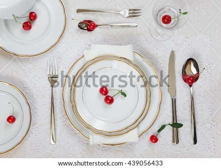 Beautifully decorated table with white plates, crystal glasses, linen napkin, cutlery and red cherries on luxurious tablecloths; top view - stock photo