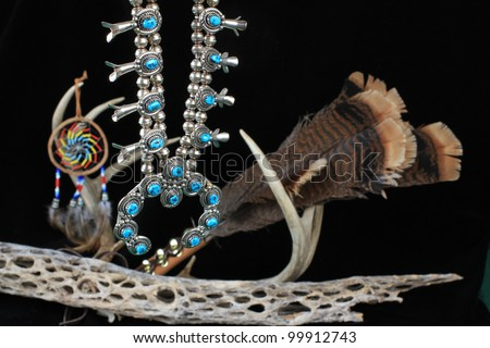 Beautifully handcrafted silver and turquoise Native American squash blossom hanging with religious and spiritual artifacts as background. - stock photo