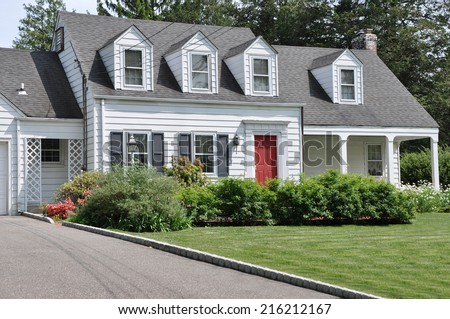 Beautifully Landscaped Suburban Cape Cod Colonial Style Home Sunny Residential Neighborhood USA - stock photo