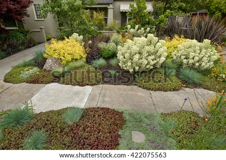 Beautifully lanscaped front yard, from street, side walk and then the house, feeling of privacy - stock photo
