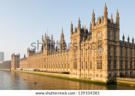 beautifully lit by the early morning sun at dawn, the British Parliament westminster at full glory on the side of river Thames in London, UK - stock photo