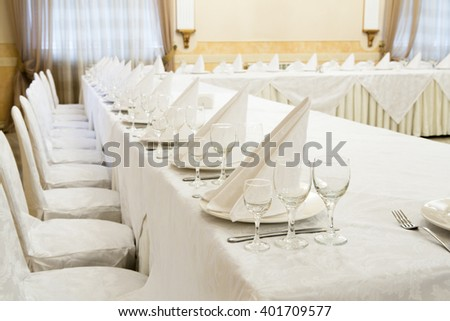 Beautifully organized event - served festive white tables ready for guests.  Event in restaurant. Banquet, wedding decor, celebration. Catering and event. Wedding tables. Large restaurant hall.  - stock photo