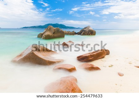 Beautifully shaped granite boulders and a perfect white sand at Anse Gaulettes, La Digue island, Seychelles. Long exposure - stock photo