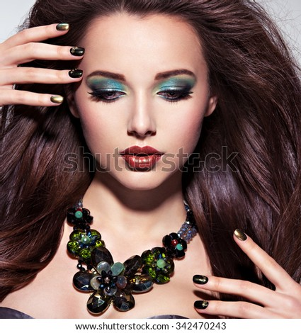 Beautiul  woman with  long brown hairs, turquoise make-up and nails - stock photo
