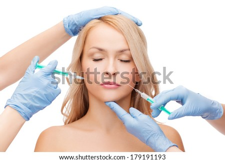 beauty and cosmetic surgery concept - woman with closed eyes and beautician hands with syringes - stock photo