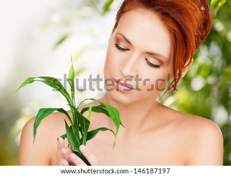 beauty and eco cosmetology concept - beautiful woman on nature with green sprout - stock photo