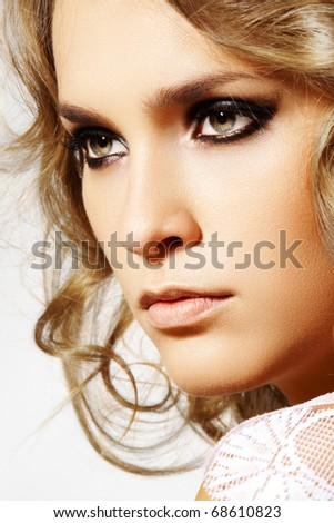 Beauty and health, cosmetics and make-up. Close-up portrait of beautiful woman model with long curly shiny hair, lace on shoulders, dark evening make-up - stock photo