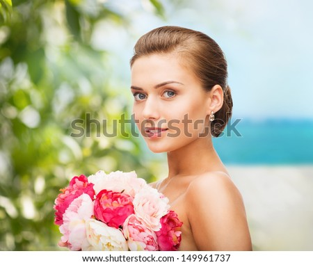beauty and jewelry concept - woman wearing earrings and holding flowers - stock photo