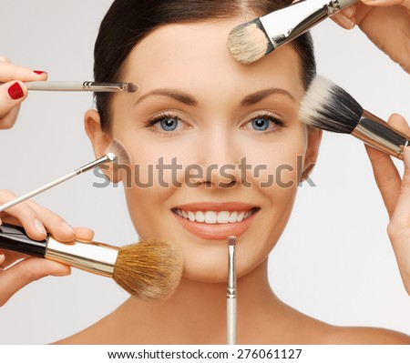 beauty and makeup concept - closeup portrait of beautiful woman getting professional make-up with many brushes - stock photo