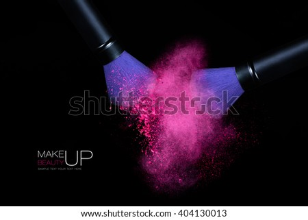 Beauty and Makeup concept. Stop action view of two makeup brushes applying matching neon pink powder over black background. Colorful dust explosion - stock photo