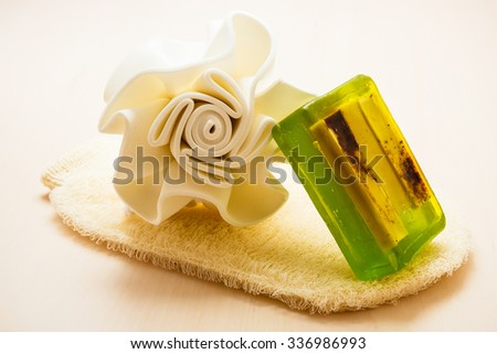 Beauty and skin care. Closeup spa products bath accessories sponge green soap and massage scrub glove on wooden table. - stock photo