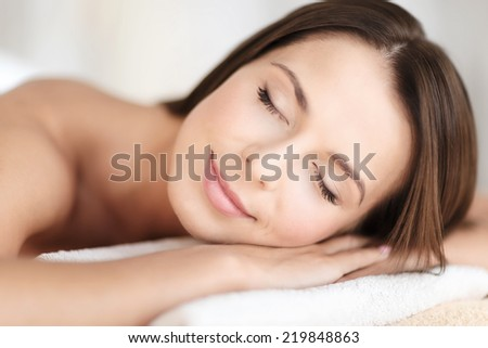 beauty and spa concept - beautiful woman with closed eyes in spa salon lying on the massage desk - stock photo