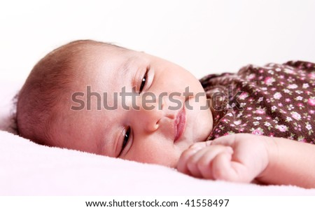 Beauty baby dreaming on white blanket. - stock photo