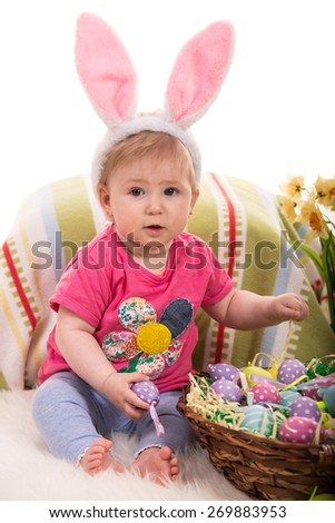 Beauty baby with pink bunny ears holding easter eggs  and sitting on fluffy blanket - stock photo