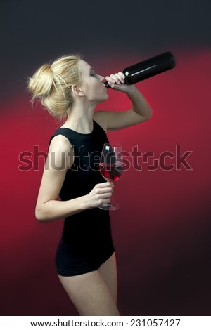 beauty blond model holding wineglass with red wine and wine bottle drinking from bottle  - stock photo