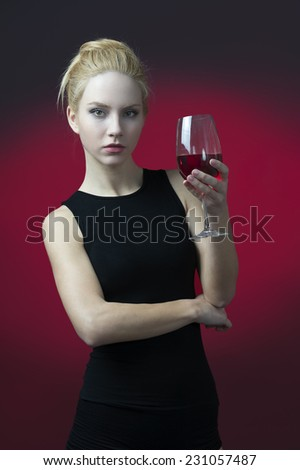 beauty blond model holding wineglass with red wine looking serious into camera  - stock photo