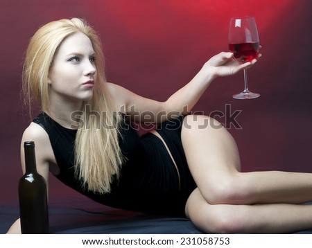 beauty blond model lying holding wineglass looking away from camera  - stock photo