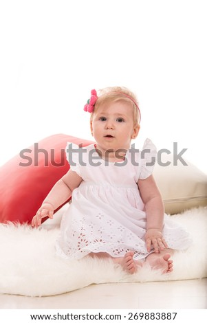 Beauty blonde baby girl with headband with flower sitting on fluffy blanket - stock photo