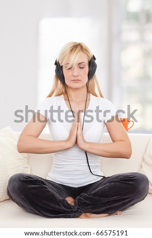 Beauty, blondie woman in a yoga position listening music with earphones - stock photo