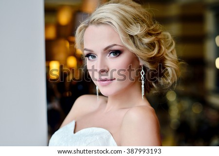 Beauty bride in bridal gown with lace veil indoors. Beautiful model girl in a white wedding dress. Female portrait of cute lady. Woman with hairstyle - stock photo