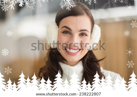 Beauty brunette with ear muffs smiling at camera against fir tree forest and snowflakes - stock photo