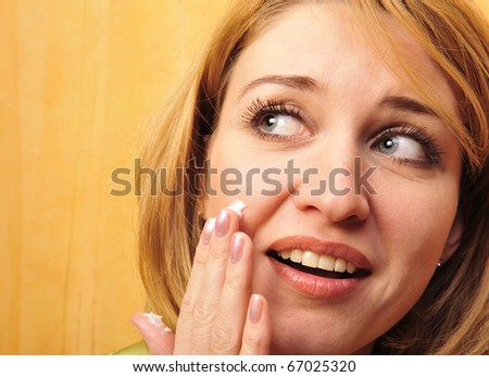 Beauty caucasian young woman applying cosmetic on face - stock photo
