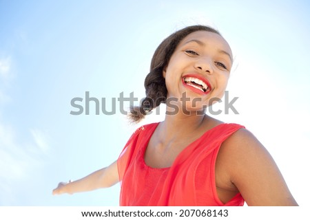 Beauty close up portrait of a young attractive african american teenager girl enjoying a sunny summer day, joyfully smiling against a blue sky during a holiday. Healthy lifestyle, outdoors. - stock photo