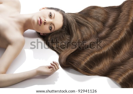 beauty close-up portrait of beautiful female face with long dark waved hairs laying down on the white, she looks in to the lens and her left arm is raised. - stock photo