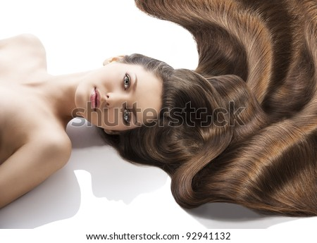 beauty close-up portrait of beautiful female face with long dark waved hairs laying down on the white. she is in front of the camera, looks in to the lens with happy expression - stock photo