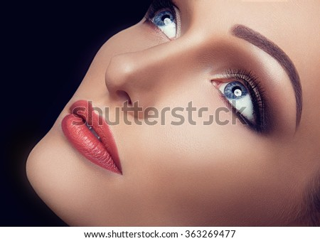Beauty Close-up Portrait of Beautiful Sexy Woman Model with Brown Fashion Eyes Make-up and Red Lips on Black Background. Vintage Toning and Color - stock photo