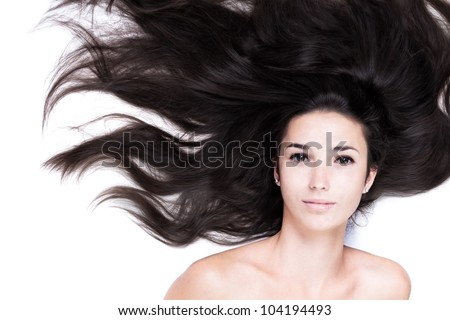 beauty close-up portrait of female face with long dark waved hairs laying down on the white. Her voluminous black hair is like the waves of the sea. beautiful woman looks with happy expression. - stock photo