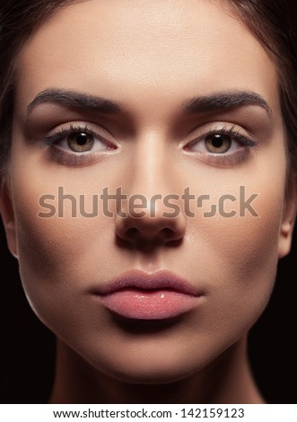 Beauty closeup of fresh young female. Beautiful bright eyes, tied brown hair, daily natural make-up and lips covered with caviar. Dark background. - stock photo