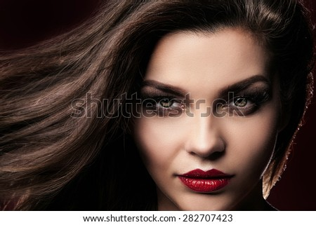 Beauty closeup portrait of attractive elegant brunette woman with red lips and long hair. Luxury lady looking at camera. Perfect makeup.  - stock photo