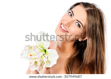 Beauty concept. Smiling young woman with clean fresh skin posing with tender flower. Skincare, bodycare. Spa. Isolated over white. - stock photo