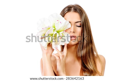 Beauty concept. Tender young woman with clean fresh skin posing with white flower. Skincare, bodycare. Spa. Isolated over white. - stock photo