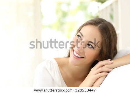 Beauty confident woman looking sideways sitting on a couch at home - stock photo