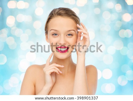 beauty, cosmetics, people and health concept - smiling young woman with pink lipstick on lips touching her face over blue holidays lights background - stock photo