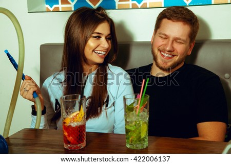 Beauty couple having fun at the bar with hookah and cocktails - stock photo