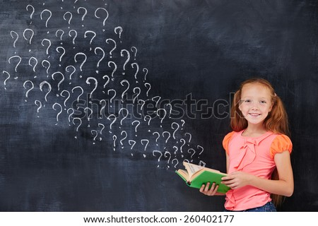 Beauty cute little ginger girl holding a book on the blackboard background - stock photo