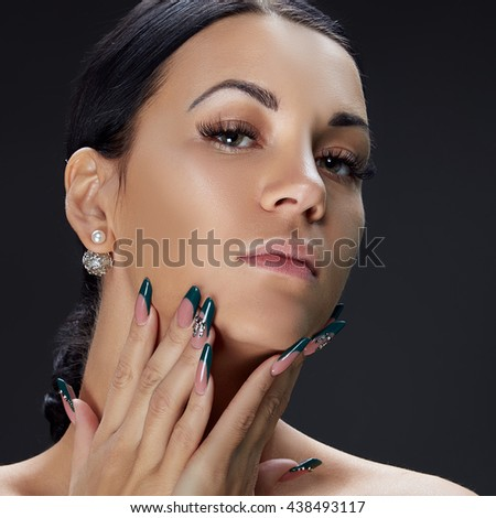 Beauty face of caucasian brunette woman with perfect nails. Isolated on black background.  - stock photo