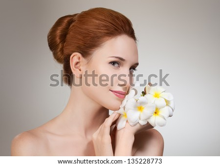 Beauty face of the young beautiful woman with flower. - stock photo