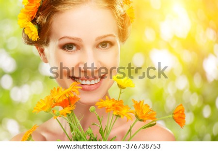Beauty face of the young beautiful woman with orange yellow flowers in her hair - stock photo