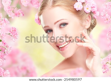 Beauty face of the young happy beautiful woman with pink flowers in her hair - stock photo